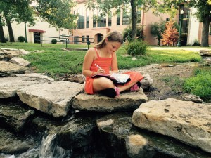 Annie studying her bible in the serene surroundings of the Baker University campus.